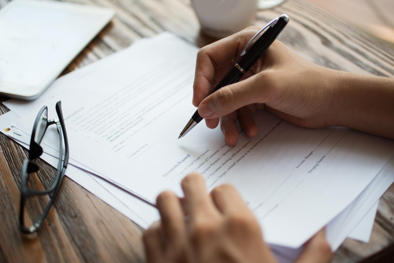 Długopis w dłoni, składanie podpisu na regulaminie