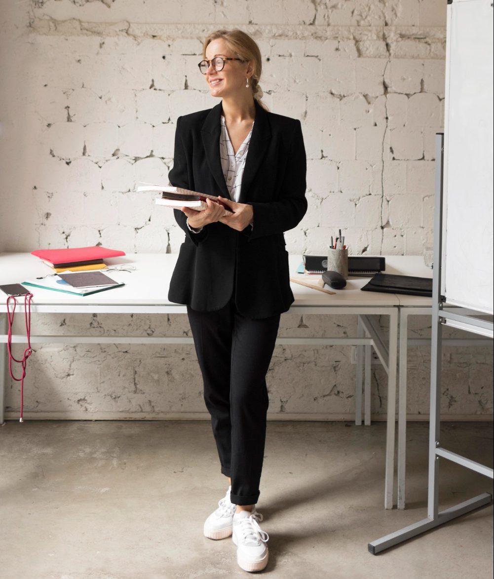 Młoda kobieta w stroju biznesowym trzymająca notatki w rękach