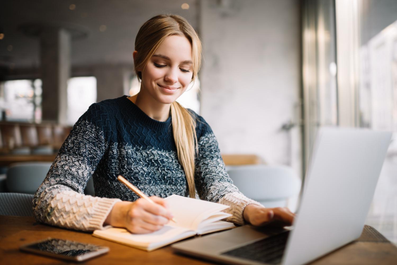 Studentka pisze w zeszycie przy użyciu ołówka