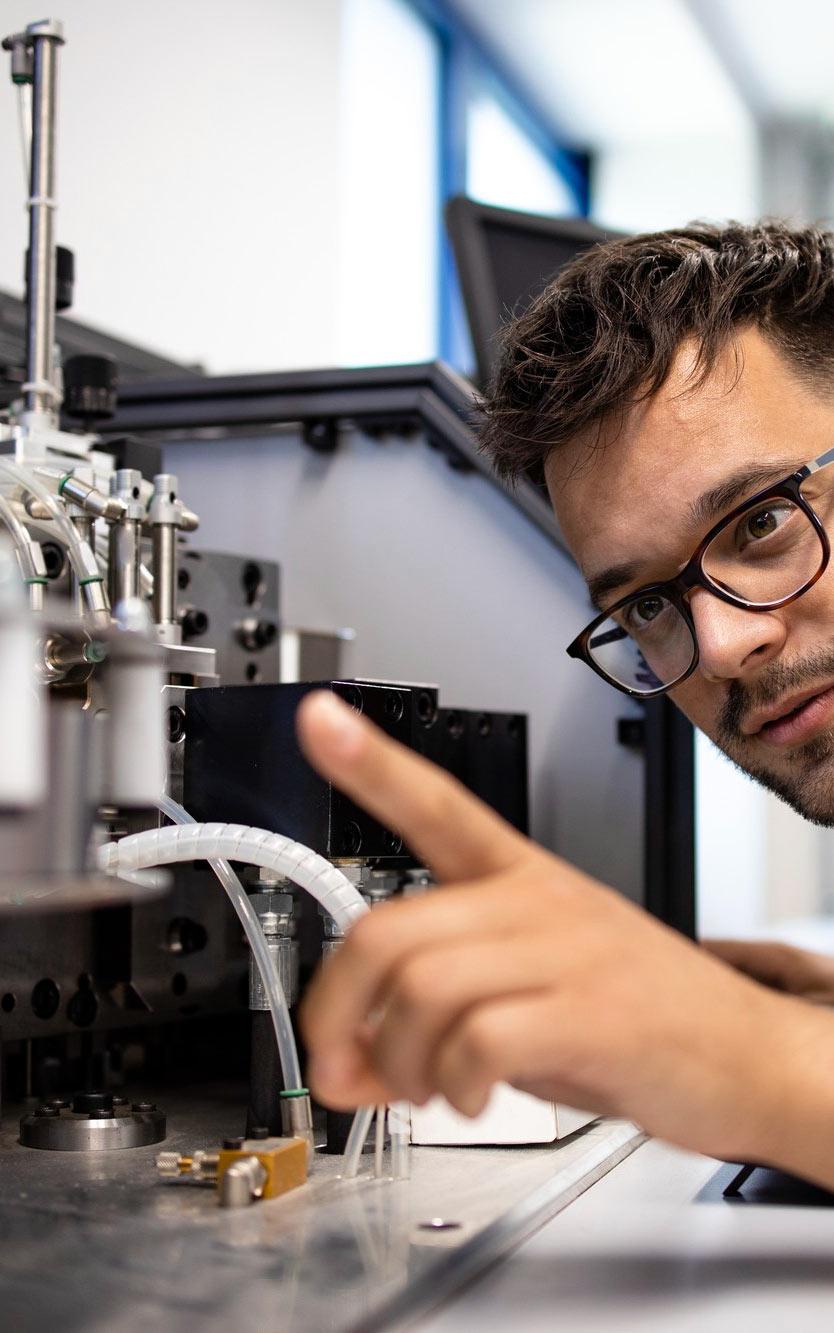 Młody człowiek pracuje przy nowoczesnym urządzeniu