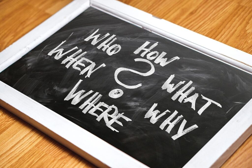 Tablica z pytaniami: WHO HOW WHEN WHAT? pisanymi kredą