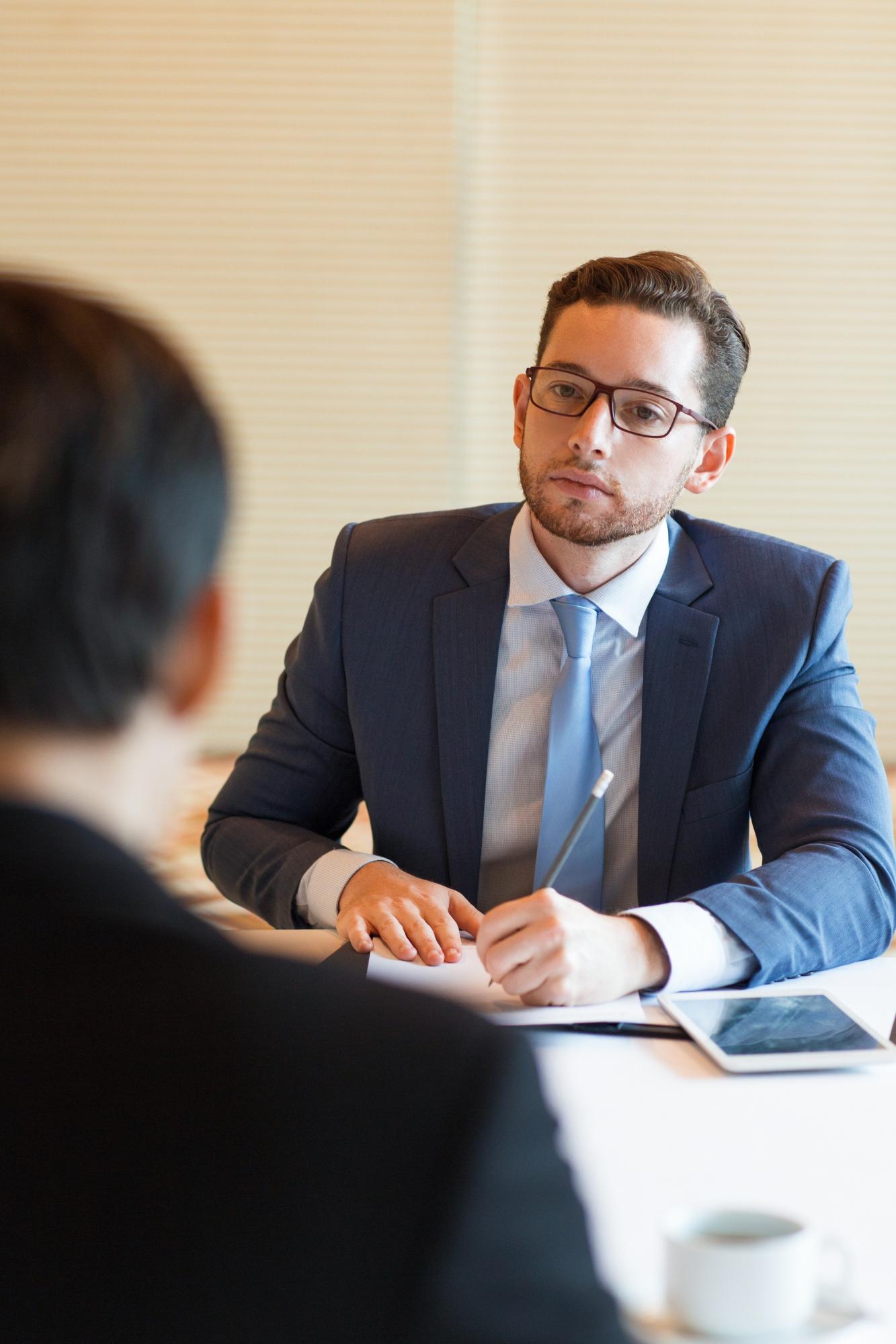 Mężczyzna w garniturze prowadzi rozmowę kwalifikacyjną
